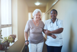 Elder and nurse walking together